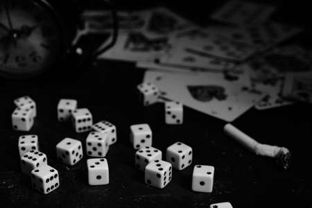 Dice,cigarettes, cards, and an abandoned alarm clock on a table in an underground casino.In black and white Stok Fotoğraf