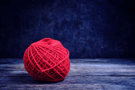 Red ball of wool yarn on a wooden table against a concrete wall