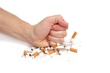 Man crushes cigarettes with his fist refusing to smoke.On white background Stok Fotoğraf