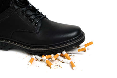 Black Shoe crushes cigarettes on a white background.Refusal of smoking Stok Fotoğraf