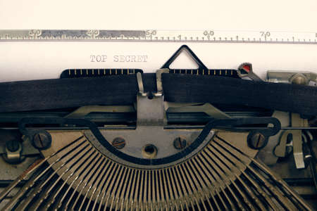 Old retro vintage typewriter. A white sheet with the printed text top secret
