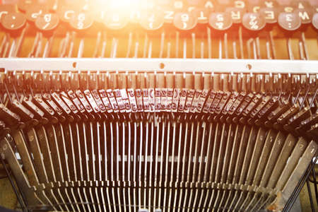 Mechanism of typesetting strikers with the English alphabet in an old retro typewriter.Solar glare