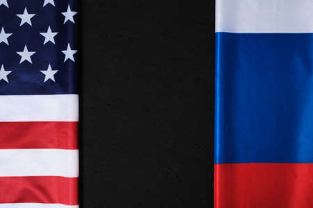 Flags of the United States of America and the Russian Federation are opposite each other on a black background