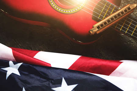 Star spangled banner, guitar and harmonica in the sunlight.Musical instrument and the flag of the United States
