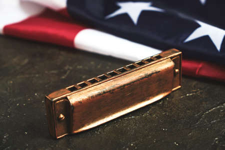 Harmonica on the background of the flag of the United States of America. Musical instrument.Stars and stripes