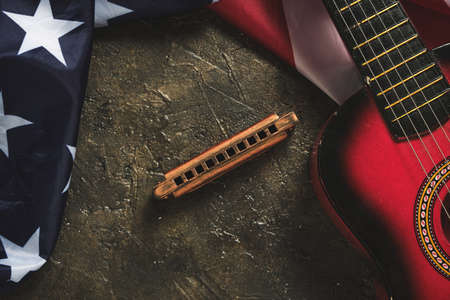 Star spangled flag, guitar and harmonica on a dark background. Musical instrument and flag of the United States of America