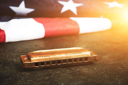 Harmonica on background of the flag of the United States of America. Musical instrument.Stars and stripes in sunlight