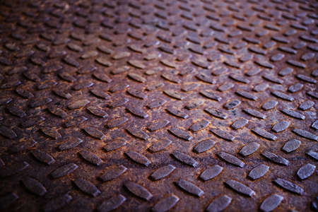 Old and rusty metal floor. Texture of a rough metal sheet with a convex pattern