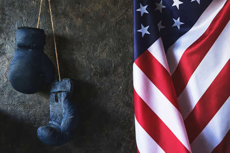 Old Boxing gloves hang on the wall next to the flag of the United States of America Standard-Bild