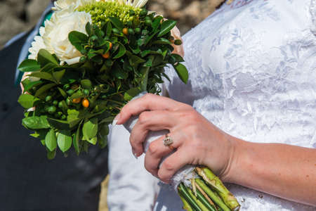 husband and wife: the bride holding a bouquet in his hand on the wedding ceremony