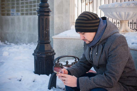 warmly: warmly dressed man sitting on a bench in the park and looks at phone Stock Photo