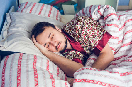 young unshaven: young unshaven man sleeping in bed Stock Photo