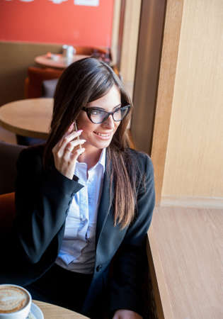 speaks: Business woman speaks by phone in a cafe and smiling