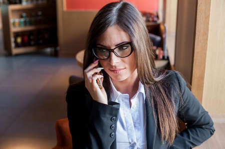 frowns: Young woman in glasses talking on the phone in a cafe and looks upset. She frowns and unhappy