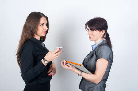 one people: Two business women standing facing each other, holding your phone or tablet and smiling