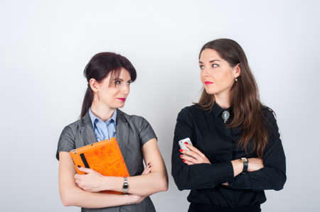 2 persons only: Two business women standing on a light background with your arms crossed and holding a tablet and phone. Looking at each other