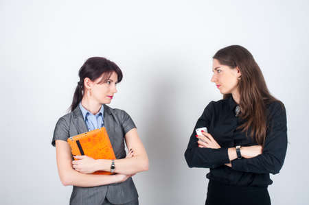 aggressively: Two business women standing on a light background with your arms crossed and holding a tablet and phone. Looking aggressively at each other
