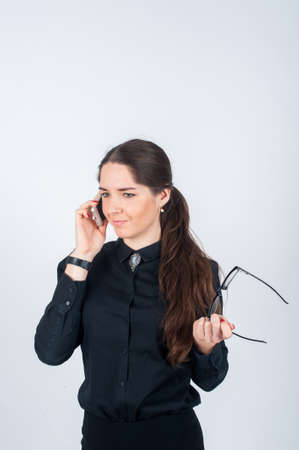 telephone saleswoman: Business woman stands on a light background, talking on the phone, keep the glasses and frowns