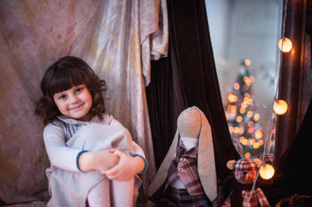 baby open present: girl sitting hugging her knees next to the mirror where lights garland