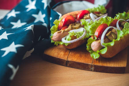 two fresh hot dogs on a wooden Board, glasses with Cola and American flag