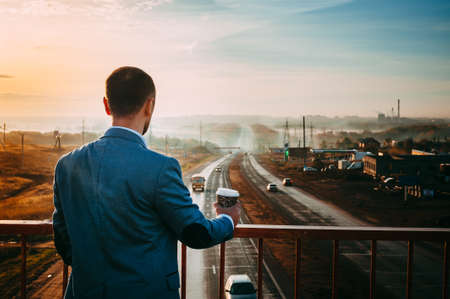 disappears: Man with Cup of coffee on the bridge. Early morning, the sunrise, the road disappears in the distance