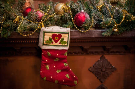 christmas lights display: Red Christmas sock hanging on the fireplace. Spruce branches, toys Christmas mood.