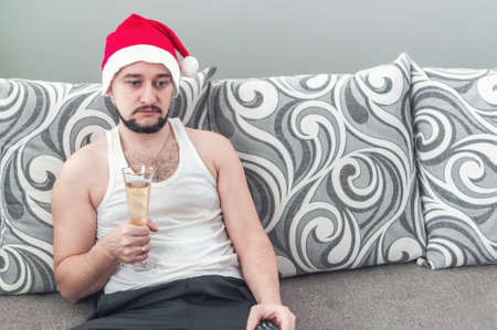Sad young man lying on the sofa at Christmas. A lazy guy in a Christmas hat drinking champagne. Stock Photo