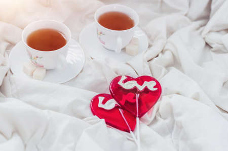 enamorados en la cama: Breakfast in bed in Valentines day. Cup of tea and sweet candies. Love or holiday concept.