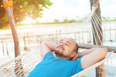 Time for laziness. The man lies in a hammock and enjoys the rest.