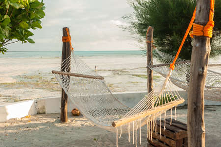 Wicker hammock, white sand and palm trees. Tropical Seating area.