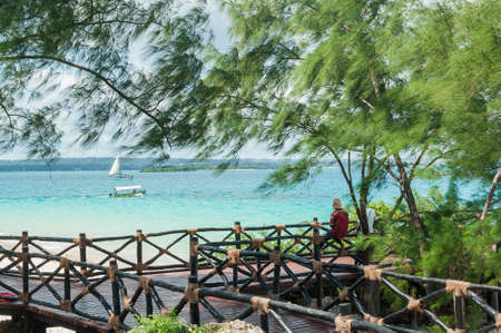 Beautiful ocean view in the Park with wooden paths surrounded by tropical trees.