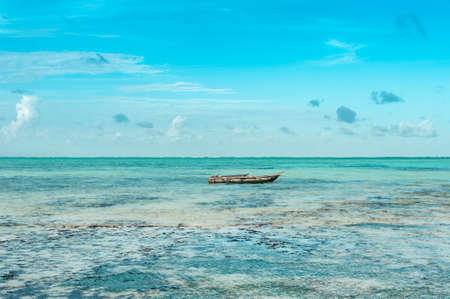 Fishermans boat swinging on turquoise waves in the Indian ocean near the shore of the island of Zanzibar. Фото со стока