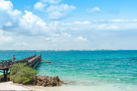 The wooden pier goes into the blue ocean. Tropical landscape with turquoise sea on the island of Zanzibar.