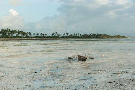 Traditional fishing boat on the sand at low tide. Landscape on the island of Zanzibar, Tanzania Фото со стока