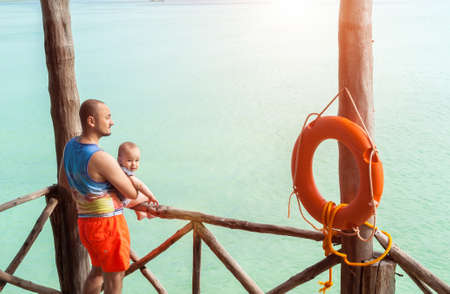 Portrait of happy dad and son on vacation. Cheerful beautiful family on the background of the turquoise sea. Фото со стока
