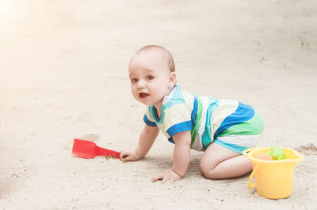 A little boy playing on a white sand. Child with toys for the sandbox. Baby crawling on a sandy beach.