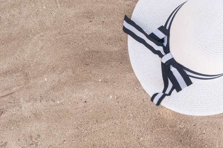 A white hat with wide brim and a seashell lie on the fine light sand. Background with beach accessories. Фото со стока