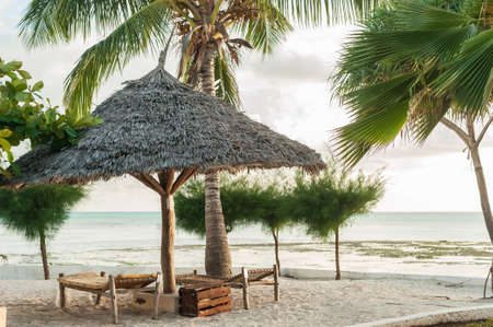 Sun loungers on the white sand and an umbrella of palm leaves in the Golden glow of the tropical sun. Фото со стока