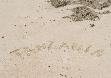 Inscription Zanzibar, Tanzania on the light sand on the beach at low tide. Фото со стока
