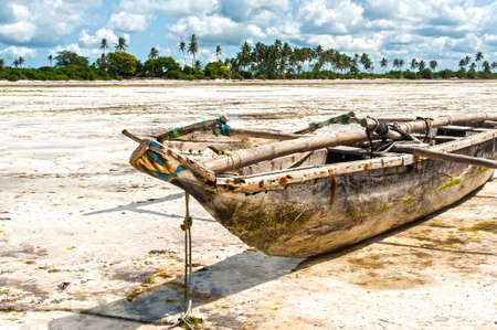 Fishing boat on the sand at low tide on Jambiani beach, Zanzibar island, Tanzania. Beautiful card with local flavor.