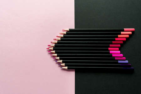Colored pencils on a pink and black background. Pencil color gradient, top view