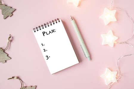 Biała kartka notesu z celami, stylowym długopisem i zieloną rośliną na różowym tle. Świąteczne lampki i zabawki, planowanie nowego życia