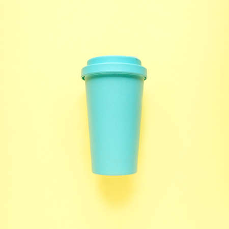 Turquoise bamboo coffee mug on yellow background. Environmental consumption, care for the world, recycling