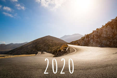 The 2020 numbers are written on the asphalt on a mountain road. Mountain serpentine goes up in the light of the bright sun. Concept for new year 2020