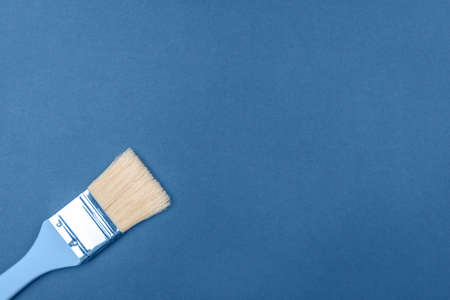 Brush with natural bristles on a blue background. The main color concept, flat lay, space for text