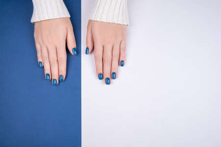 Stylish womens manicure on a blue-gray background. Fashionable womens manicure in blue. Stylish manicure, great design for any purposes. Health care concept.