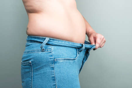 Full female body in jeans. Large postpartum belly. The concept of losing weight by summer. The concept of postpartum recovery