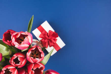 Delicate blue background with a bouquet of red tulips and a gift. Greeting card for Mothers Day, March 8, Birthday, Valentines Day. Space for text, flat lay