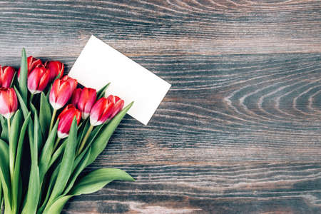Beautiful pink tulips and a white postcard on a wooden background. Space for text Banque d'images - 140627879