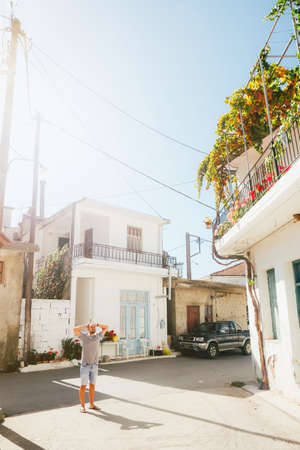 A young man stands in the middle of a street in a European village. Non-standard routes for travel. Trips by car. The architecture of Greece.